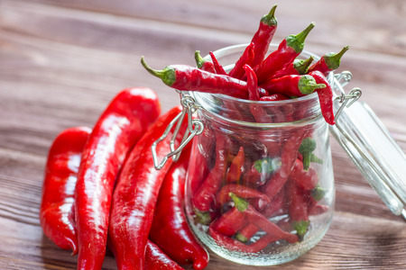narrowly: Closeup of organic red Jalapeno peppers spilling out of mason jar
