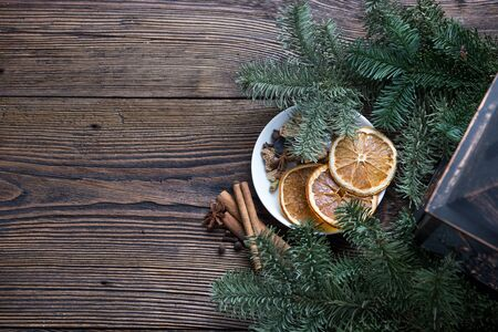 Christmas still life with vintage lamp, fir branches, white plate with dryied orange, cinnamon and anice Stock Photo