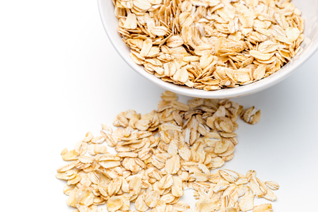 Food. Oatmeal on the table. Dry rolled oat flakes oatmeal in a white bowl on a white table. Stock Photo