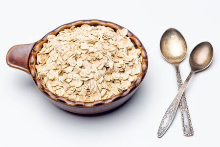 Food. Oatmeal on the table. Dry rolled oat flakes oatmeal in brown ceramic bowl