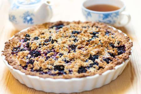 Homemade open blackberry pie served with black tea
