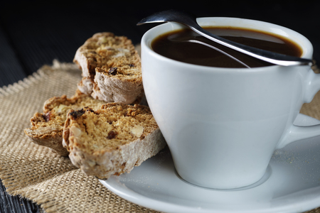 Coffee espresso in cup with italian cantucci, cookies on sackcloth, rustic style.