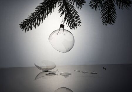 Studio photography of a broken glass christmas tree ball with lots of shards on the ground in white back Stock Photo