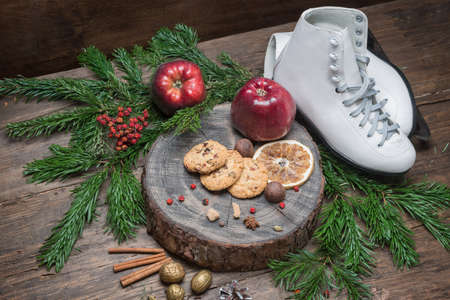 Pair of White Ice Skates and red apples on the wooden board
