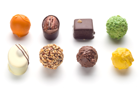 Assorted chocolates confectionery candies shot from an overhead view isolated on white.