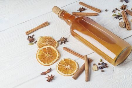 Ingredients for cooking traditional christmas orange wine. Spices, cinnamon sticks, cardamom, anise, bottle of wine, citrus fruit, ginger on white wooden background, flat lay, top view 版權商用圖片
