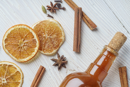 Ingredients for cooking traditional christmas orange wine. Spices, cinnamon sticks, cardamom, anise, bottle of wine, citrus fruit, ginger on white wooden background, flat lay, top view Stock Photo