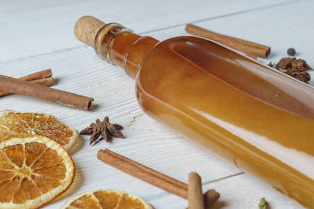 Ingredients for cooking traditional christmas orange wine. Spices, cinnamon sticks, cardamom, anise, bottle of wine, citrus fruit, ginger on white wooden background. 版權商用圖片