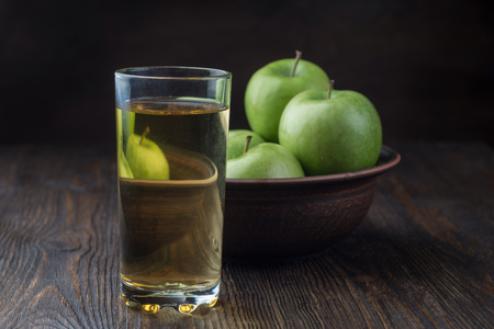 Apple juice in a glass and apples in clay bowl on wooden background Imagens