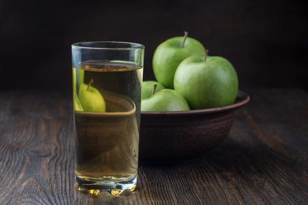 Jugo de manzana en un vaso y manzanas en un recipiente de arcilla sobre fondo de madera