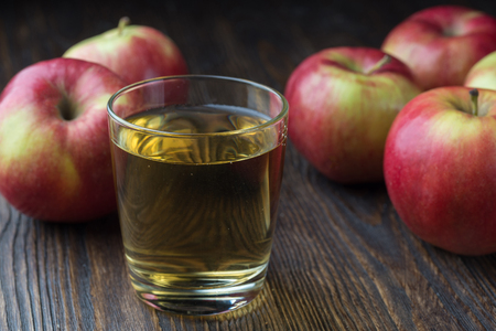 Fresh organic farm apple juice in glasses with raw whole and red apples, on old rustic wooden table, copy space Imagens