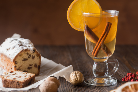 Traditional hot toddy winter drink with spices recipe. Fresh homemade cake holiday on a wooden background.