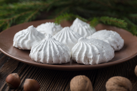 Sweet dessert white zephyr walnut and hazelnut marshmallows on clay plate and rustic christmass tree background 免版税图像