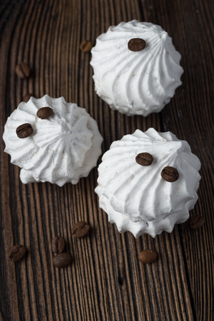 Homemade marshmallow cakes made from natural ingredients on a wooden surface with crumbled coffee beans Stok Fotoğraf