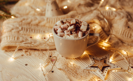 Cup of hot cocoa with marshmallows a against rustic background with Christmas fir branches of bokeh. Perfect winter time treat. Toned image. Soft focus.