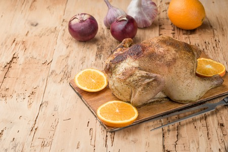 Roasted chicken with orange served on wooden board on wooden table, top view