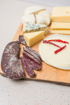 Various types of international soft , cheese, blue mold, gouda, feta and dried meat on wooden board. Фото со стока