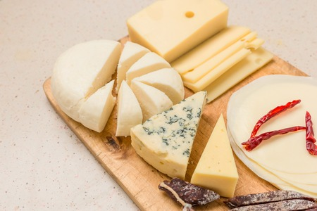 Various types of international soft , cheese, blue mold, gouda, feta and dried meat on wooden board. Imagens
