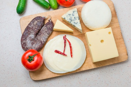Composition of different type of cheese on wooden board with fresh vegetables.