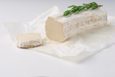 Rebanadas de queso de cabra y pieza de queso de cabra con romero sobre fondo blanco. Comer queso culinario. Foto de archivo