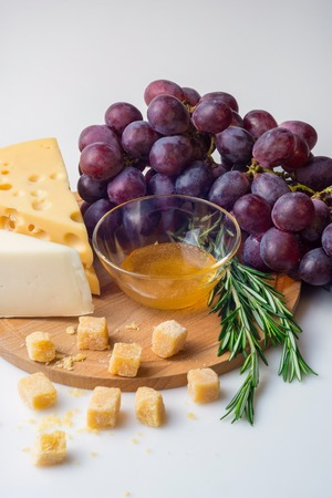 Wooden board with tasty cheese rosemary, honey and purple grapes on white background
