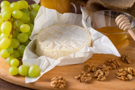 Soft Cheese and grapes, walnut, honey. Camembert with grapes and nuts, melange on a dark background.