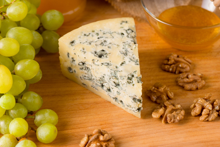 Delicious blue cheese with honey, walnuts and grapes on wooden  background.