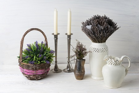 Home decorations in the interior. On the wooden background lies a vase of flowers, basket, pot and candles. Concept of comfort Reklamní fotografie