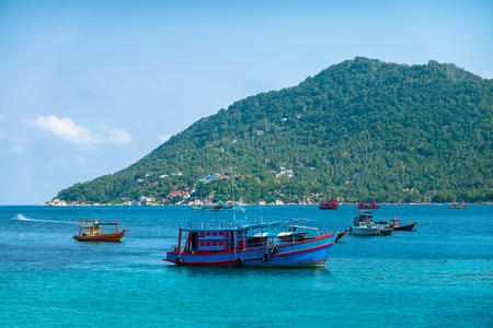 Few fisherman boats in Gulf of Thailand turquoise sea, background of small green tropical island Tay. Banque d'images