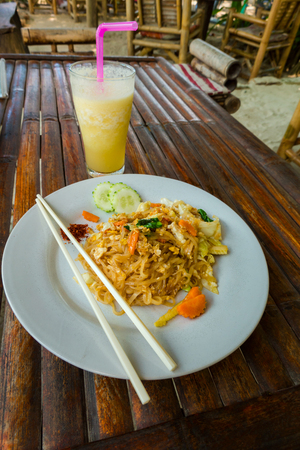 Chicken noodles, favorite meals in south east Asia. served in white plate on wooden table, cafe background.