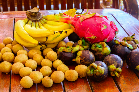 Fresh tropical fruit on wood: bananas, lychee, mangosteen, lychee, dragon fruit.
