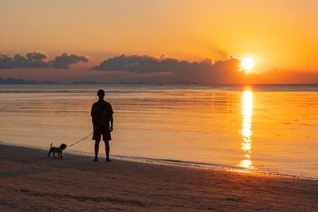 Man op zoek op zee zonsondergang in de tropen. Silhouet van staande man en zijn hond.