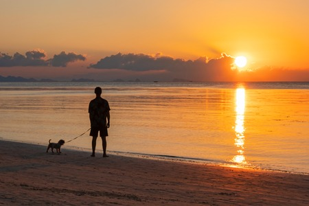 Mann, der auf Seesonnenuntergang in den Tropen schaut. Silhouette des stehenden Mannes und seines Hundes.