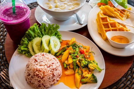 Stir-fried rice  with minced pork, chicken, fried yellow baby corn and carrot,  broccoli  in white dish on wooden background. Thai style food. Zdjęcie Seryjne