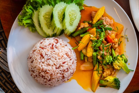 Stir-fried rice  with minced pork, chicken, fried yellow baby corn and carrot,  broccoli  in white dish on wooden background. Thai style food. Фото со стока