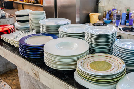 Stack of plates on the showcase. Restaurant utensils. Shallow focus