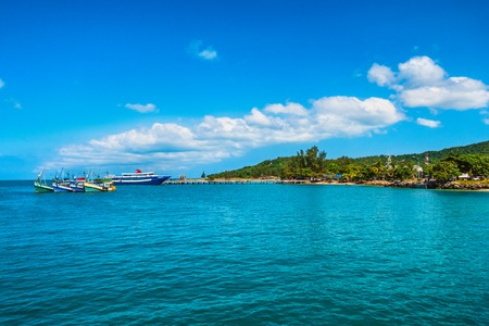 Many ships, boats, in the port and water on the tropical sea warm summer resort with palm trees against the blue sky and sand beach