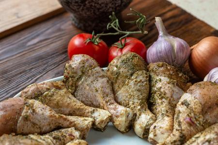 Rohe ungekochte Hühnerbeine, Trommelstöcke auf weißem Teller, rustikales Holzbrett, Fleisch mit Zutaten zum Kochen Standard-Bild