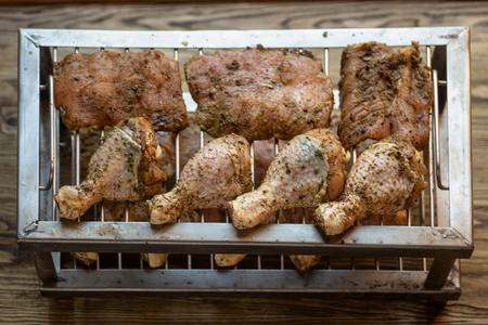 Raw marinade chicken legs on grill ready for smoking machine. Stock fotó