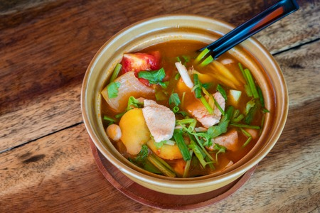 Tom Yum Gai or spicy tom yum soup with chicken - Authentic Thai style food. With ingredients: lemongrass, galangal, kaffir lime leaves, fresh chilies, and green onion. Stock Photo - 124464456