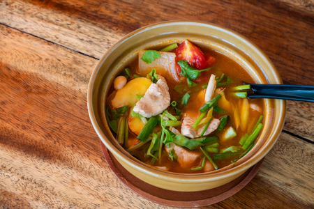 Tom Yum Gai or spicy tom yum soup with chicken - Authentic Thai style food. With ingredients: lemongrass, galangal, kaffir lime leaves, fresh chilies, and green onion.