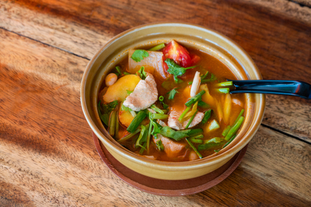 Tom Yum Gai or spicy tom yum soup with chicken - Authentic Thai style food. With ingredients: lemongrass, galangal, kaffir lime leaves, fresh chilies, and green onion. Stock Photo - 124464458