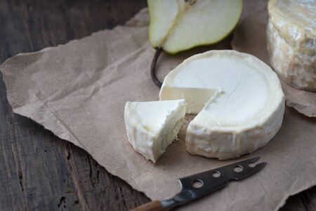 Brie type of cheese. Camembert cheese. Fresh Brie cheese and a slice on a wooden board with pear and knife. Italian, French cheese. Reklamní fotografie