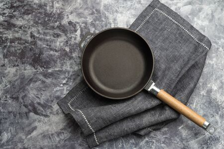Cast iron pan on rustic stone background close up - empty black frying pan frying skillet with napkin and copy space