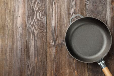 Empty cast iron frying pan on wooden culinary background, view from above.