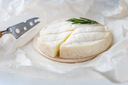 Brie type of cheese. Camembert cheese. Fresh Brie cheese and a slice on a white paper with rosemary and knfe. Italian, French cheese.