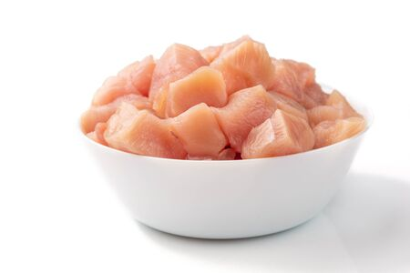 Raw chicken fillet breast cut into pieces in white bowl isolated on white background.