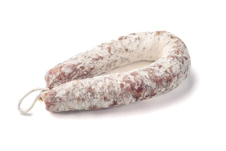 Air dried pork sausage ring of smoked meat, close-up, isolated on white background.