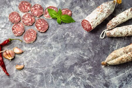A lot of pieces of dried sausage with basil leaf on a dark stone background. Minimalistic composition of food.
