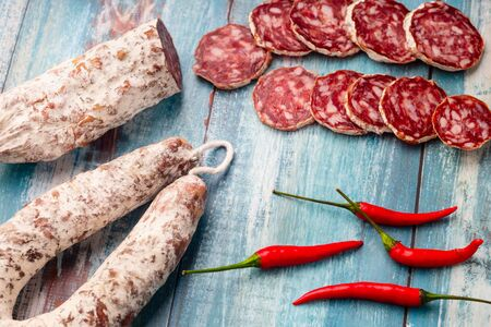 Sliced cured sausage with chili pepper on blue wooden rustic background. 免版税图像